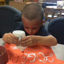 A child using glue to make letters