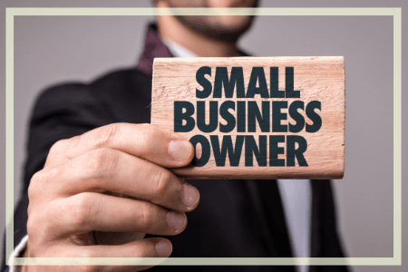 Photograph of man holding a small sign that reads Small Business Owner