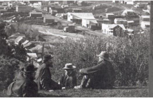 Old stereooptican image of town of Mariposa in the 1800s as seen from nearby hill with men in the fo