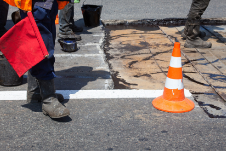 Photograph of road with hole, traffic cones, and the feet of workman standing nearby