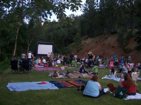Photograph of people sitting on blankets and chairs in the park in front of a large movie screen.