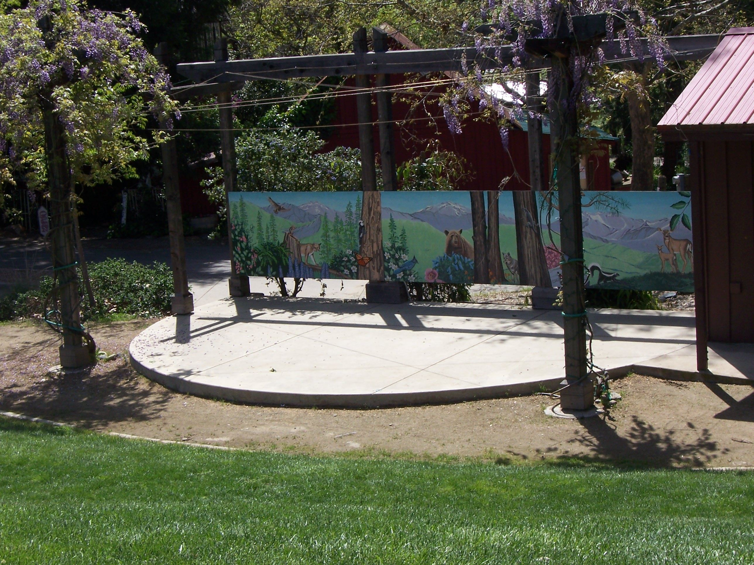 Photograph of outdoor stage with woodland mural behind and a lawn in the foreground